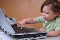 Bebé sonriente que trabaja en el escritorio de oficina Imagenes de archivo