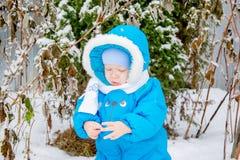 Bebé sorprendido con la primera nieve que sostiene nieve en su mano Fotos de archivo