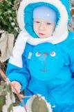 Bebé sorprendido con la primera nieve que sostiene nieve en su mano Imagen de archivo