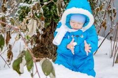 Bebé sorprendido con la primera nieve que sostiene nieve en su mano Fotografía de archivo libre de regalías