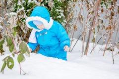 Bebé sorprendido con la primera nieve que sostiene nieve en su mano Imagenes de archivo