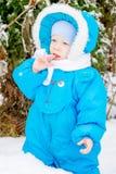 Bebé sorprendido con la primera nieve que sostiene nieve en su mano Foto de archivo