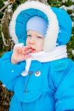 Bebé sorprendido con la primera nieve que sostiene nieve en su mano Foto de archivo libre de regalías