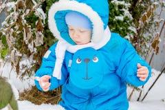 Bebé sorprendido con la primera nieve que sostiene nieve en su mano Fotos de archivo libres de regalías