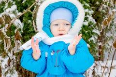 Bebé sorprendido con la primera nieve que sostiene nieve en su mano Imagen de archivo libre de regalías