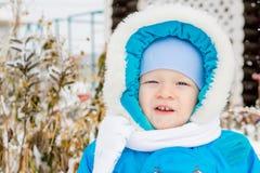 Bebé sorprendido con la primera nieve que sostiene nieve en su mano Fotografía de archivo