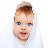 Bebé sorprendido debajo de la toalla blanca Imagen de archivo