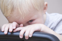 Bebé tímido que mira a escondidas sobre silla Imagen de archivo libre de regalías