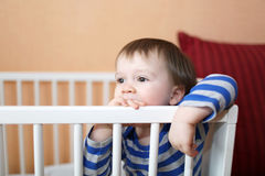 Bebé triste de 1 año en la cama blanca Imagen de archivo