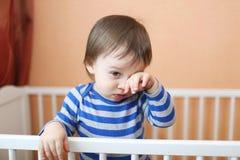 Bebé triste en la cama blanca Fotografía de archivo
