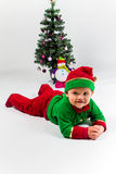 Bebé vestido como ayudante de Papá Noel que miente al lado del árbol de navidad. Imagen de archivo libre de regalías