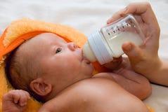 Bebé y botella que introduce Fotografía de archivo