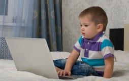 Bebé y computadora portátil. Imagen de archivo