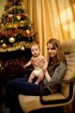 Bebé y el suyo madre cerca del árbol de navidad imagen de archivo