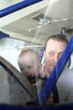 Bebé y hombre que sonríen a través del parabrisas del aeroplano Foto de archivo