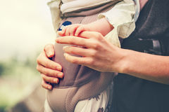 Bebé y madre que celebran el abarcamiento de las manos Imagen de archivo