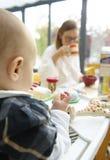 Bebé y mama en el vector de desayuno Fotos de archivo