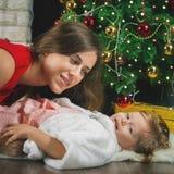 Bebé y momia divertidos cerca del árbol de navidad Año Nuevo 2017 Foto de archivo libre de regalías
