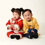 Bebé y muchacha chinos en equipo del Año Nuevo de chino tradicional Foto de archivo libre de regalías