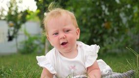 Bebé y naturaleza Fondo el echar los dientes del bebé Problemas de dentición del bebé Bebé que miente en hierba verde Niño que ju almacen de video