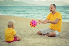Bebé y padre que juegan la bola del juguete Fotos de archivo libres de regalías