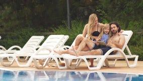 Bebé y padres que se relajan en sunbed cerca de piscina en el centro turístico Forme a las muchachas, pares, familia en el centro almacen de video