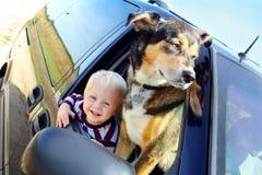 Bebé y perro felices en ventana del minivan Foto de archivo libre de regalías