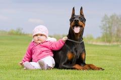 Bebé y perro negro grande Foto de archivo