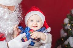 Bebé y Santa Claus felices con el regalo grande, actual caja imagenes de archivo
