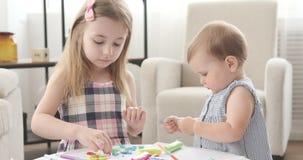 Bebé y su hermana que juegan con plasticine almacen de video