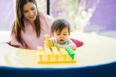 Bebé y terapeuta que juegan con los juguetes imágenes de archivo libres de regalías