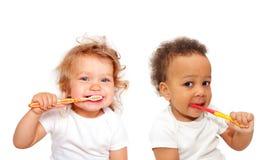 Bebés blancos y negros que cepillan los dientes Imagenes de archivo