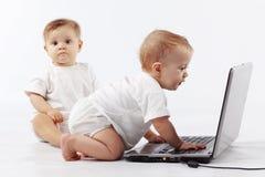 Bebés con la computadora portátil Imagen de archivo libre de regalías