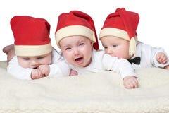 Bebés con los sombreros de santa en fondo brillante fotos de archivo