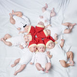 Bebés con los sombreros de santa en fondo brillante fotografía de archivo