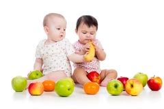 Bebés de los niños con la comida sana foto de archivo