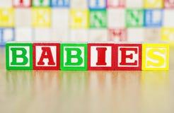 Bebés deletreados hacia fuera en bloques huecos del alfabeto Imagenes de archivo