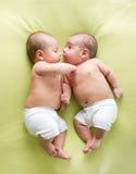 Bebés divertidos de los hermanos de gemelos que mienten en cama verde Imagen de archivo libre de regalías