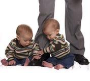 Bebés do gêmeo idêntico que prendem os pés dos paizinhos Fotografia de Stock Royalty Free