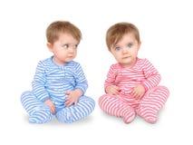 Bebés gemelos curiosos en blanco Foto de archivo