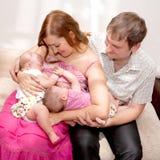 Bebés gemelos de amamantamiento en casa Fotos de archivo