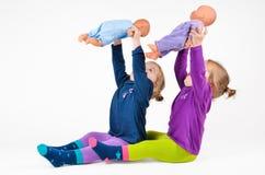 Bebés gemelos que juegan con los dols Imágenes de archivo libres de regalías