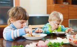 Bebés que comen en la tabla de madera Fotos de archivo