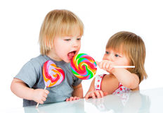 Bebés que comen un lollipop pegajoso Imagen de archivo