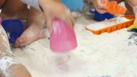 Bebés que juegan con la harina blanca en cuidado de niños de la guardería almacen de video
