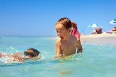 Bebés que têm o divertimento na água de mar na praia Imagem de Stock Royalty Free