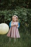 Bebê à moda que guarda o balão grande que veste o vestido cor-de-rosa na moda no prado playful Festa de anos foto de stock