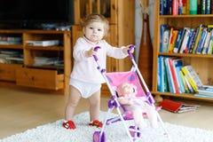 Bebê adorável bonito que faz primeiras etapas com transporte da boneca fotografia de stock royalty free