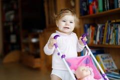 Bebê adorável bonito que faz primeiras etapas com transporte da boneca imagem de stock royalty free