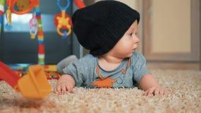 Bebê adorável em um chapéu com os brinquedos que encontram-se no assoalho em casa vídeos de arquivo